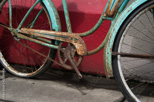 Plexiglas Fiets Vintage rusty bike without pedals over a red wall