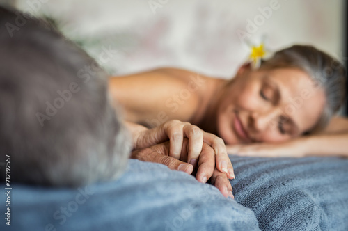 Leinwanddruck Bild Mature couple holding hands at spa