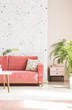 Leinwanddruck Bild - Plant next to pink couch with pillow in living room interior with patterned wallpaper. Real photo
