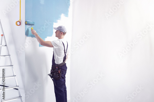 Decorator wearing a overall painting a room on a blue color. Place your graphic/tool/logo on the empty wall