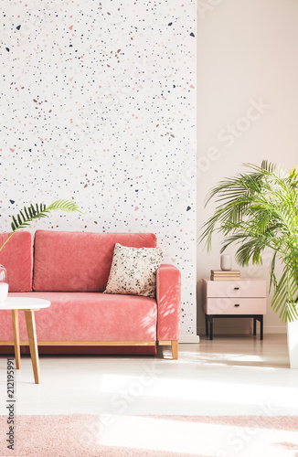 Leinwanddruck Bild Plant next to pink couch with pillow in living room interior with patterned wallpaper. Real photo