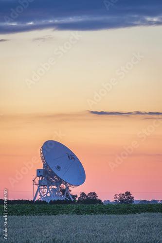Fototapeta Colorful sunset sky over radiotelescope antenna at astronomy observatory, Piwnice, Torun, Poland