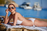 happy beautiful young woman in  bikini and sunglasses posing on the beach sea - 212197397