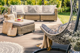 Pillows on rattan couch and table on patio with hanging chair during summer. Real photo - 212201191
