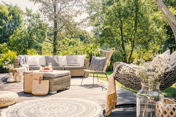 Patterned pillow on rattan chair next to sofa on terrace with rug in the garden. Real photo © Photographee.eu