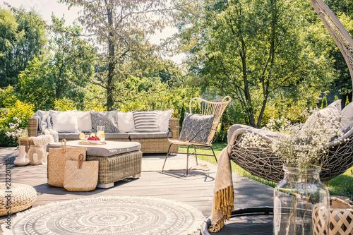 Wzorzysta poduszka na rattan krześle obok kanapy na tarasie z dywanikiem w ogródzie. Prawdziwe zdjęcie
