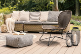 Patterned pouf and rattan chair on wooden patio with pillows on sofa and lanterns. Real photo - 212201920