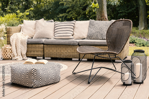 Leinwanddruck Bild Patterned pouf and rattan chair on wooden patio with pillows on sofa and lanterns. Real photo
