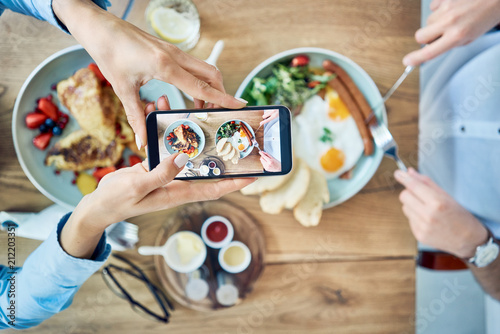 Fototapeta Woman taking photo of breakfast served in cafe. Couple having meal together