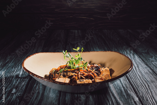 soba with tofu and vegetables decorated with germinated seeds of sunflower on plate on wooden table