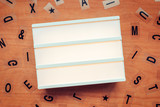 Blank lightbox and letters on wooden background - 212212918