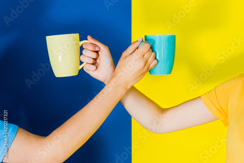 Cropped view of colorful cups in women hands on blue and yellow background - 212217321