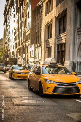 Street view in New York City in midtown Manhattan with yellow taxi cabs and buildings.
