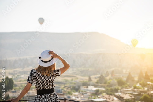 The girl standing on the terrace and staring into the distance on the balloons in the sky. Turkey. Cappadocia.