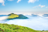 Green mountain peak in the clouds