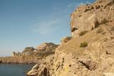 Mountain landscape, rocks and reefs surrounding the blue Bay of the Black sea. Crimea.