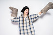 Leinwanddruck Bild - funny Russian girl with pigtails in a warm fur hat posing and smiling, holding felt boots in hands