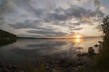 gray evening sky over the lake, orange sun, fish-eye
