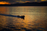 The fisherman are cruising to the ocean for fishing on beautiful golden sunrise