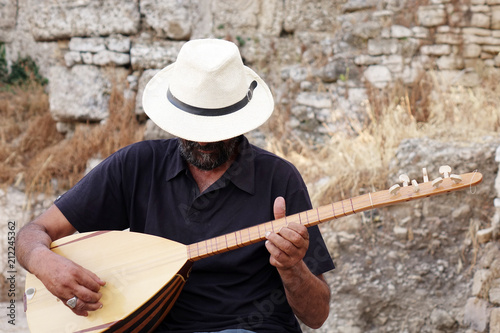 A street musician plays a Turkish instrument. A man in a white hat plays a game of baglama. - 212245362