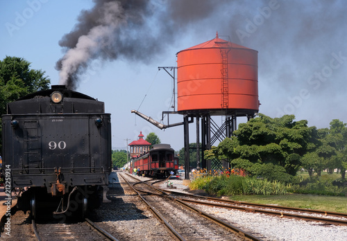 Steam train pulling up to the water tower to fill up in the railroad yard in color