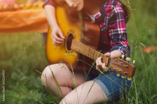 Beautiful girl with dark hair playing guitar in field. Young girl wearing denim shorts and pleated button up shirt sitting in grass field playing guitar. - 212261927