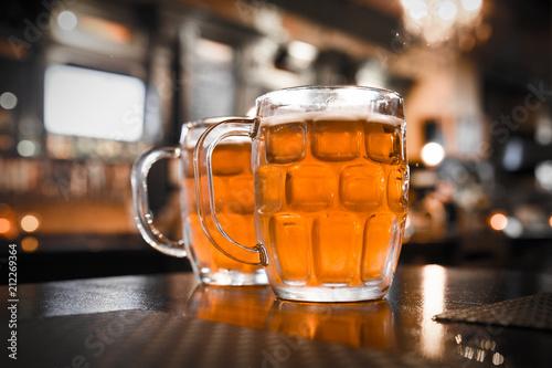 Fototapeta Two glass mugs of cold bar in a typical Irish pub setting