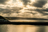 Beautiful view of Whitby pier with light emerging between the clouds
