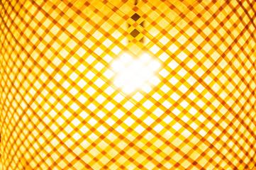 Light bulb glowing inside wooden shade closeup © Greg Brave