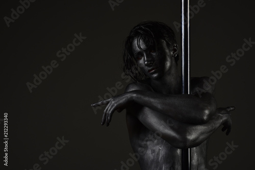 dance on pylon. dance on pole by silver body man, copy space.