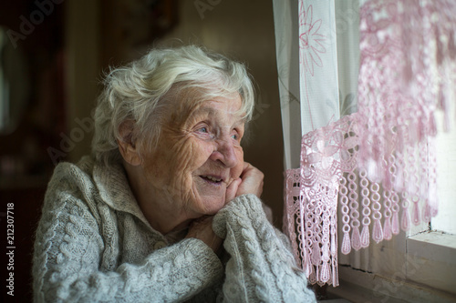 Foto Murales A gray-haired elderly woman sits and looks out the window.