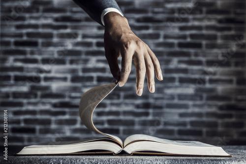 開かれたページを持つ人の手