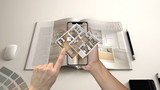 Augmented reality concept. Hand holding smartphone with AR application used to simulate 3d pop-up interactive house maps to life - 212310751