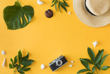 Flat lay design of yellow background with laptop, photo camera, green palm tropical leaf and flowers, top view. Summer background, vacations and holidays, trip and travel planning concept