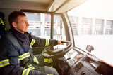 smiling fireman at the wheel of a fire truck drives to work