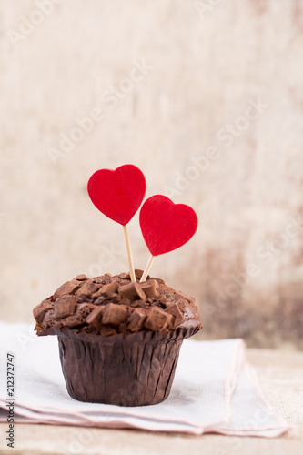 Homemade chocolate muffins with heart, vintage background.