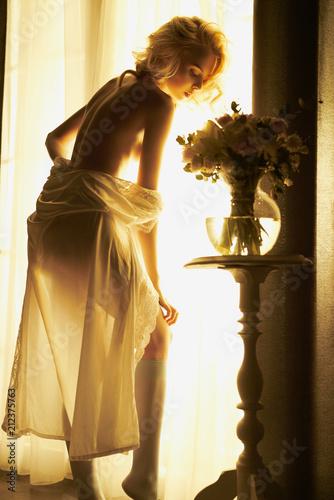 Fotobehang womenART Sensual blonde at the window