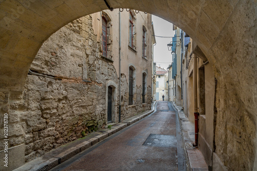 Fototapeta Looking Through an Arch into a Narrow Cobblestoned Street In Tarascon, France