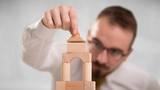 Young handsome businessman using wooden building blocks  - 212382521