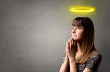Young woman praying on a grey background with a shiny yellow halo above her head - 212382541