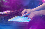 Hand mixing music on midi controller with party club colors around  - 212383915
