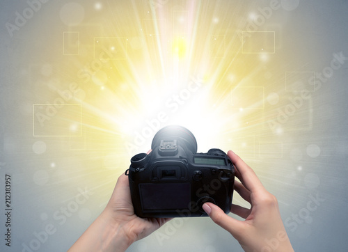 Leinwanddruck Bild Naked hand taking picture with digital camera and glowing flash concept