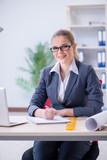 Businesswoman working at her desk in office - 212384111