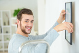 happy man positioning picture frame on wall - 212385706