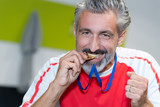 man biting the gold medal - 212385984