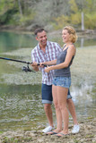 happy couple fishing by the pond - 212385996