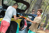 teenage lads unloading surf equipment from their vehicle - 212390179