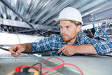 electrician sets the lamp on the ceiling - 212391947