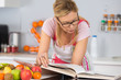 mature woman reading cookbook in the kitchen looking for recipe