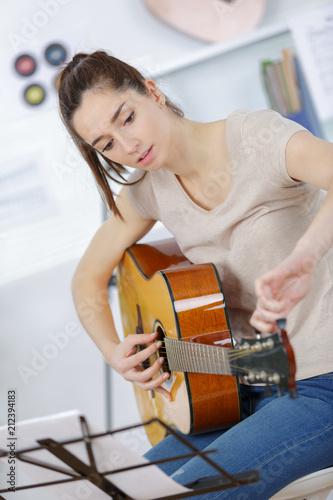 Fototapeta young woman tuning the guitar